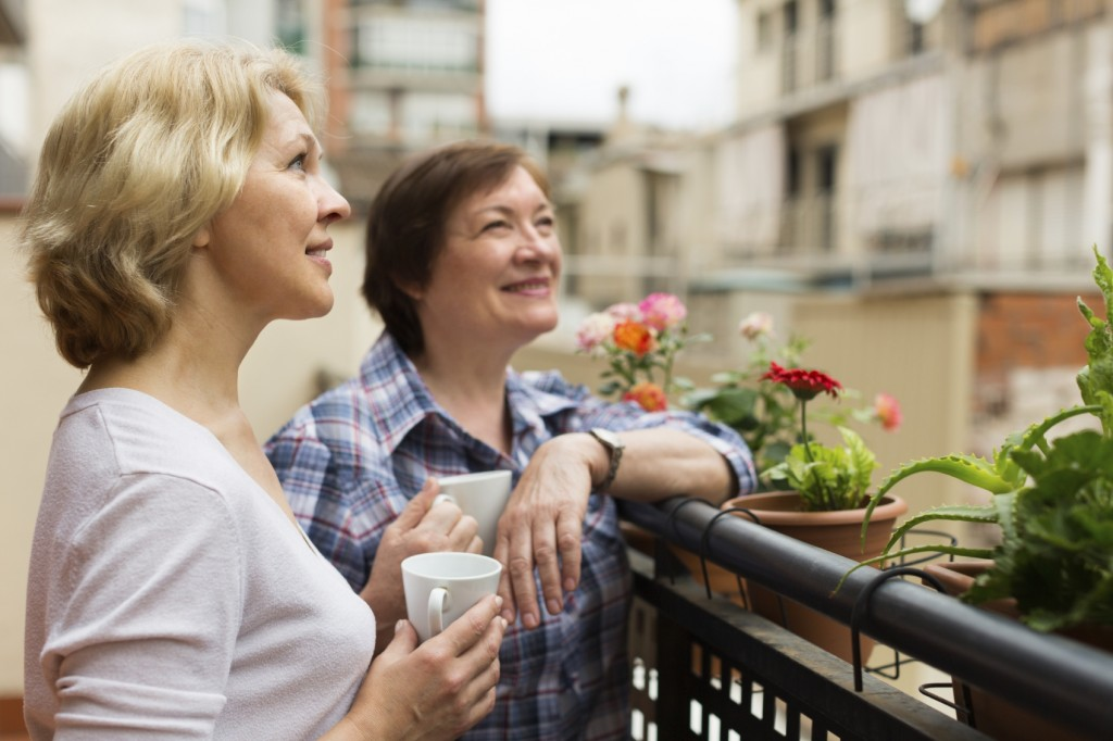 Smiling aged female friends relaxing with cup of coffee on balcony